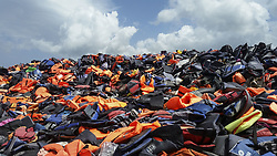 August 11, 2016 - Lesvos, Greece - Piles of lifejackets in Lesvos island, about 10m high on 11 August 2016. Cheap and crappy lifejackets were sold in Turkey. About 500.000 lifejackets are gathered here near Molivos in Lesvos island from the 2015 arrivals. Also the Chinese Ai Weiwei artist took many of them in Berlin and exhibited them in a public building. Thousands of people drawned between Greece and Turkey as the dinghies were in bad condition and the lifejackets didn't work. In 2015 there were days that there were more than 5000 refugee arrivals daily. (Credit Image: © Nicolas Economou/NurPhoto via ZUMA Press)