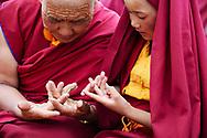 During the teachings of the Dalai Lama in Zanskar, a senior nun is taking care of her community by teaching a young one the Mandala offering mudra (gesture) - Padum, Zanskar, Jammu-Kashmir, India, 2012