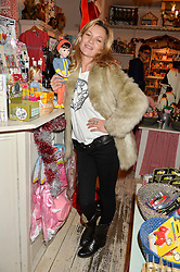KATE MOSS with the A Girl For All Time doll at a promotional party for the A Girl For All Time doll held at HoneyJam, 2 Blenheim Crescent, London on 5th December 2015.