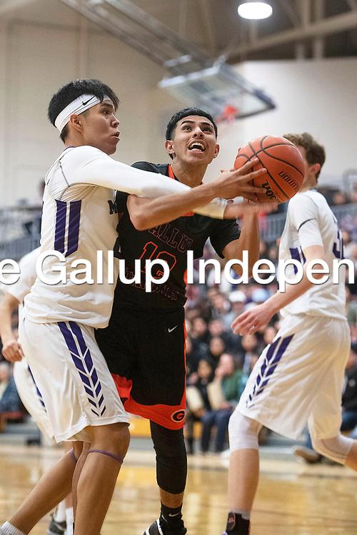 Gallup Bengal Isaac Bustinza (12) drives to the basket while Miyamura Patriot Isiah Begay (23) defends Friday night at Miyamura High School in Gallup. Gallup took the win 76-46.