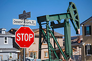 Oil well and pumpjacks near housing developments in the City of Signal Hill. Once a massive oil producing area, oil wells are still mixed in its now residential neighborhoods. Los Angeles Coutny, California, USA