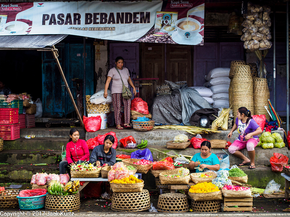 """07 AUGUST 2017 - BEBANDEM, BALI, INDONESIA: Women weave baskets in the market in Bebandem, in far eastern Bali. """"Pasar"""" is the Indonesian word for market. The market is known for baskets, which are woven in the area. Bali's local markets are open on an every three day rotating schedule because venders travel from town to town. Before modern refrigeration and convenience stores became common place on Bali, markets were thriving community gatherings. Fewer people shop at markets now as more and more consumers go to convenience stores and more families have refrigerators.     PHOTO BY JACK KURTZ"""