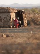 Maasai tribesman sitting outside an Inkajijik, a traditional Maasai house. South-east Kenya, Kenya