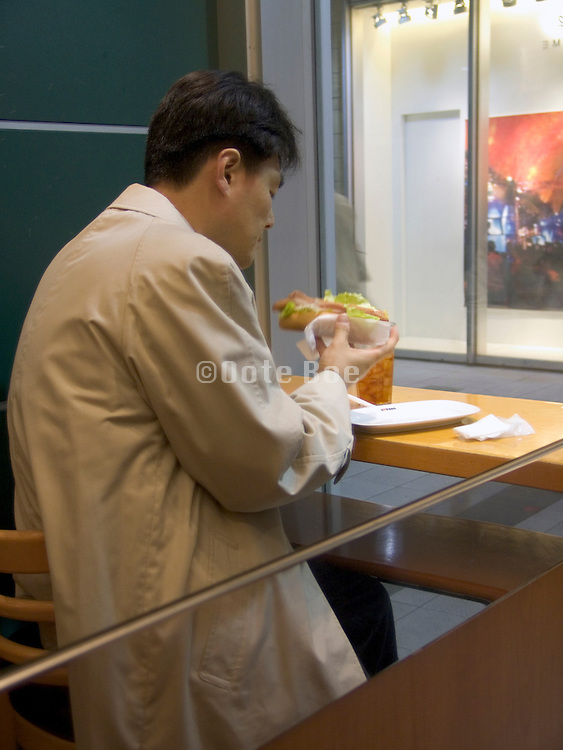 Businessman eating a sandwich during his lunch break
