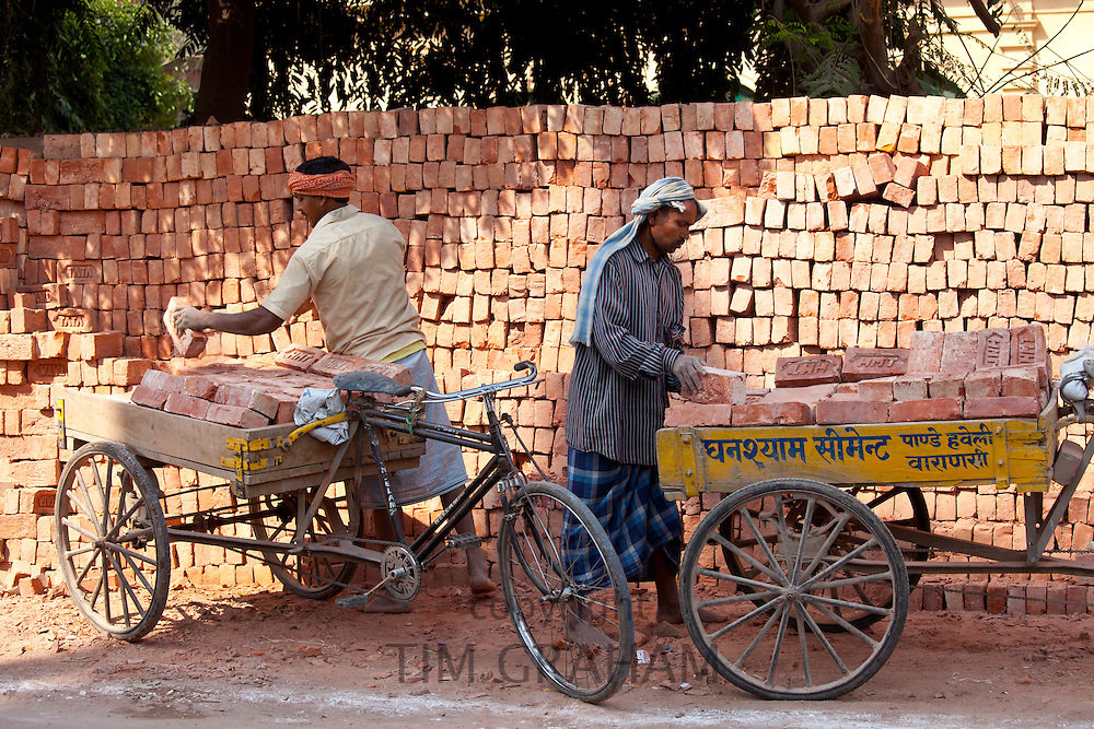 Indian men stacking TATA bricks in the city of Varanasi, Benares, Northern India