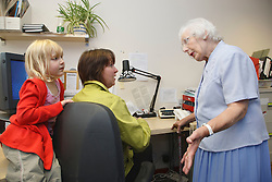 Woman in office trying to work, being disturbed by family members.