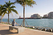 A senior citizen stting on the quayside at South Pointe Park lookig out at Biscayne Bay