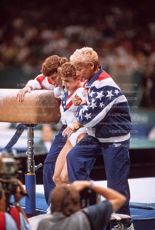 ATLANTA - JULY 23:  Kerri Strug of the United States is assisted off the mat by coach Martha Karolyi (right) and another team official after her second vault in the team competition of the Women's Gymnastics event of the 1996 Summer Olympic Games held on July 23, 1996 in the Georgia Dome in Atlanta, Georgia.  Strug was part of the gold medal winning USA Women's team, nicknamed the Magnificent Seven.  (Photo by David Madison/Getty Images)
