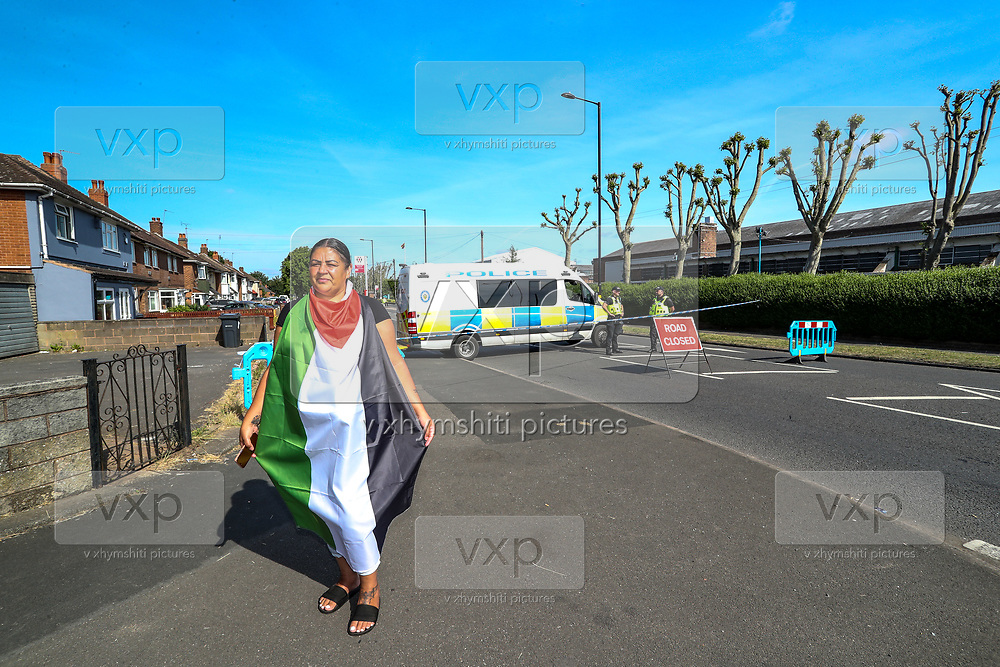 Birmingham, United Kingdom, June 15, 2021: A woman wearing a Palestinian flag pose for a picture nearby an Arconic factory site in Birmingham on June 15, 2021 - to support Palestine Action demonstration. Activists from 'Palestine Action' continues to occupy an American industrial factory known as Arconic in Birmingham. This is a protest against the company who they say 'provided cladding for Grenfell Tower' and 'materials for Israel's fighter jets.' (Photo by Vudi Xhymshiti)