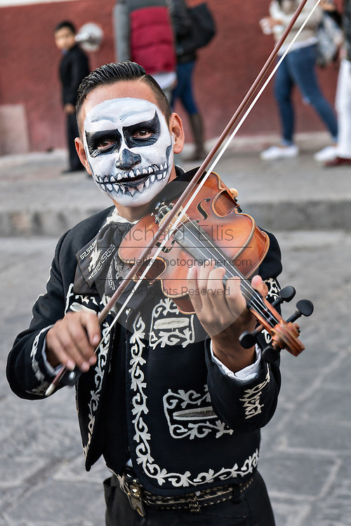 A mariachi dressed as a skeleton for the Day of the Dead festival performs in the Jardin Principal October 28, 2016 in San Miguel de Allende, Guanajuato, Mexico. The week-long celebration is a time when Mexicans welcome the dead back to earth for a visit and celebrate life.
