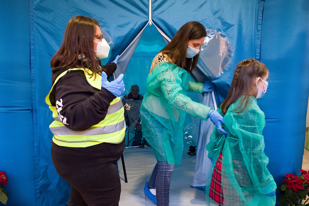 A mother and her daughter wearing a protective suit against the spread of the novel coronavirus COVID-19 exit from a 'hug room', a special room where people can meet their relatives through a plastic sheet to keep people safe from COVID-19 infection at a care home in Santa Lucia di Serino, province of Avellino, southern Italy, on January 2, 2021.