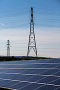 Solar panels and electricity pylons at the Solar array of community project Low carbon Gordano, a community renewable energy project. Delivering 1,750HWh per annum. Avon, Somerset.