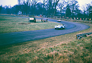 """British Sports racing driver Bill de Selincourt (1921-2014) driving Lister-Jaguar """" Knobbly"""" car, BARC event at Oulton Park circuit, Cheshire, England 17th March 1962 - out of focus"""