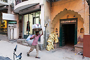 A street vendor passes a modern upscale shop in the trendy village of Sharpur Jat now home to expensive couture and the burgeoning fashion industry. New Delhi, India