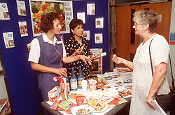 Women handing out information leaflets and answering questions at health exhibition stall,