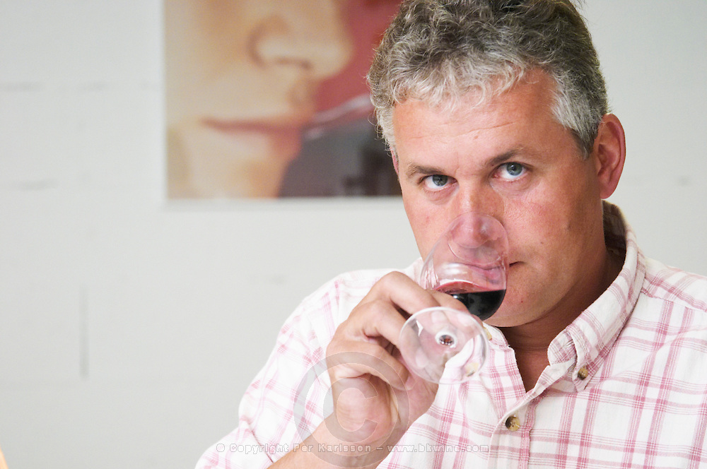 Joel Durand tasting a glass of wine. In the background a poster with a young woman sniffing a glass of wine.  Domaine Eric et Joel Joël Durand, Ardeche, Ardèche, France, Europe