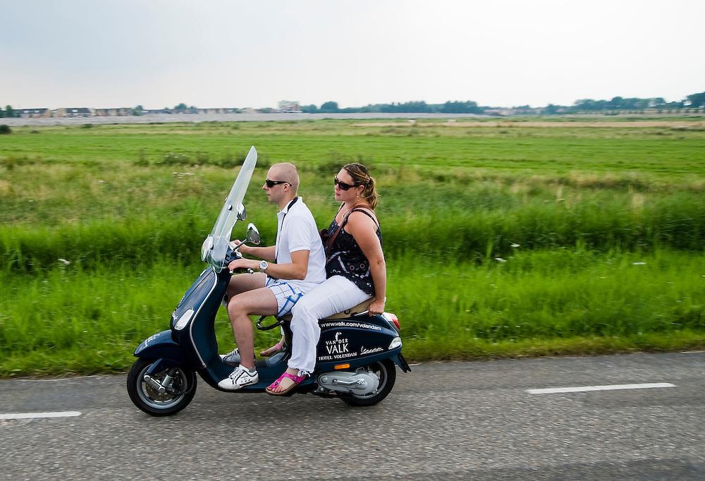 Nederland, Edam, 5 juli  2009.Jongen en meisje op scooter rijden langs weiland. Meisje achterop scooter. Dit zijn toeristen, want de scooter is van van der Valk hotel en ze zitten er niet op alsof ze het gewend zijn. ..Foto (c) Michiel Wijnbergh