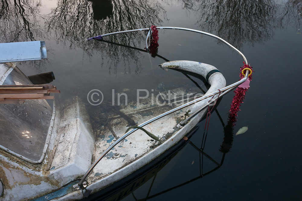 A moored narrow boat lies partially submerged with Christmas tinsel still attached to the bow rail, on 2nd January 2017, in Regents Canal, central London, England.