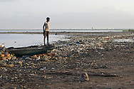 July 8, 2012 - A young girl stands on the bow of a fishing boat docked on the shoreline of Cité Soleil at dawn in Haiti. Many children are expected to help family members fetch water, repair nets or sort through the fishing catch as the day begins.<br /> (photo by Meghan Dhaliwal)