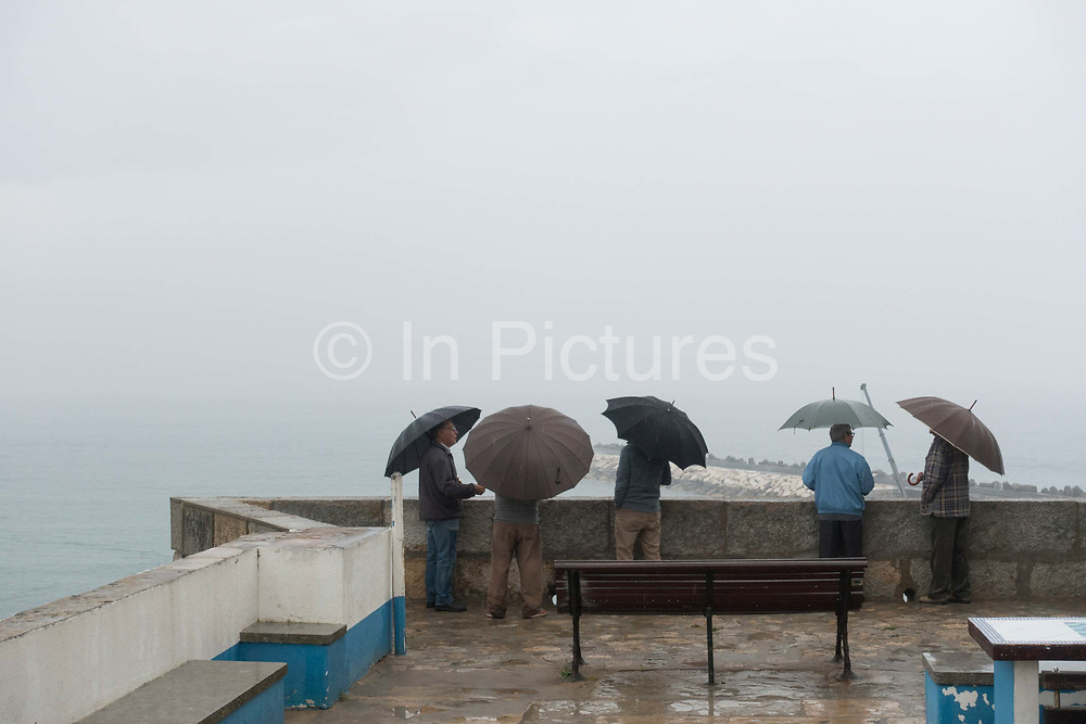 Five Portuguese men with umbrellas looking out to sea at Fisherman's Beach on 25th May 2018 in Ericeira in Portugal. Ericeira is a civil parish and seaside resort/fishing community on the western coast of Portugal.