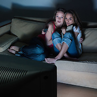 pictures in a living room of two young girls sitting on a couch watching on tv a scary movie