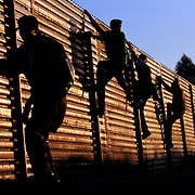 Undocumented migrants flee back toward Mexico after being chased by the U.S. Border Patrol along the U.S.-Mexico border in San Diego, California. <br /> <br /> Photo registered with the US Copyright Office. © Todd Bigelow<br /> <br /> Please contact Todd Bigelow directly with your licensing requests. <br /> <br /> PLEASE CONTACT TODD BIGELOW DIRECTLY WITH YOUR LICENSING REQUEST. THANK YOU!