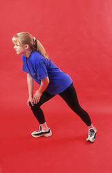 Teenage girl stretching while exercising,