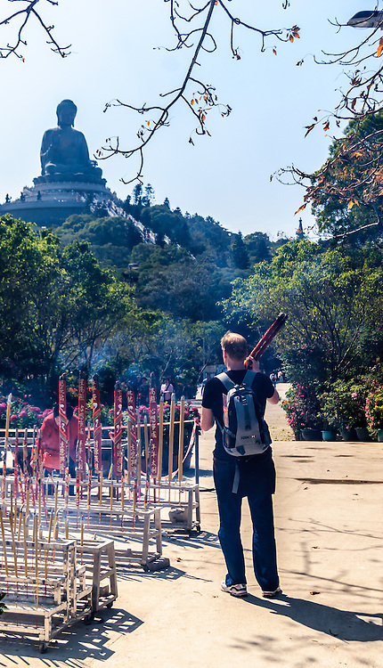 A visitor with incense sticks praying The Tian Tan Buddha on Lantau Island, Hong Kong. Po Lin Monastery is a major center of Buddhism in Hong Kong and is also a popular tourist attraction.