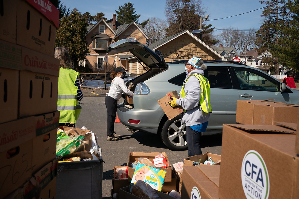 Volunteers load food packages into clients' cars at the Center for Food Action in Englewood, NJ, on March 9, 2021.