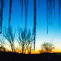 Beautiful winter sky after sunset with icicles hanging from the roof framing the view.