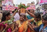 The women carrying the pot are believed to possess the spirit of Mother Goddess Mahankali and people are trying to console her in front of the Mahankali<br /> temple in Hyderabad, India on 07/21/2019. When they walk towards the temple, people pour water on their feet to pacify the spirit, who, by nature, is<br /> believed to be aggressive. Photo by Akash Pamarthy