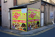 Pizza business advertising on a street corner in Harrogate, North Yorkshire. The hoarding has been wrapped around the back of a business in a side street of this North Yorkshire town, otherwise known for its quaint tea rooms and health spas. Pizza Parada are offering Buy One Get One Free (aka BOGOF) and show illustrated versions of their pizzas, burgers and wraps.