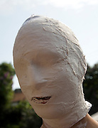 Model released young man's face covered in white bandage tape as art project