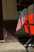 Close up of USA flag and bicycle Taxi on old town street, Havana, Cuba