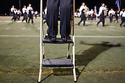 Milpitas High School senior and Drum Major Johnathan Yeung stands on a ladder to lead the marching band during a half-time performance against Woodside at Milpitas High School in Milpitas, California, on September 13, 2013. The Trojans went on to beat the Wildcats 50-6. (Stan Olszewski/SOSKIphoto)