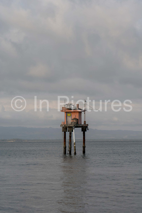 A tall fisherman's watch tower off shore at Batu Karas beach on the 31st October 2019 in Java in Indonesia.