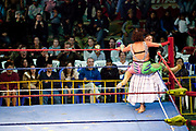 Two 2 female wrestlers in ring, one being slammed against ropes in corner. Lucha Libre wrestling origniated in Mexico, but is popular in other latin Amercian countries, including in La Paz / El Alto, Bolivia. Male and female fighters participate in the theatrical staged fights to an adoring crowd of locals and foreigners alike.