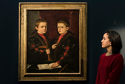 """© Licensed to London News Pictures. 02/12/2016. London, UK. A staff member views """"Portrait of two boys, said to be Members of the Pesaro Family"""" by Tiziano Vecellio, called Titian, (est. GBP 1-1.5m), at a preview of Sotheby's upcoming Old Masters Evening Sale in New Bond Street. Photo credit : Stephen Chung/LNP"""