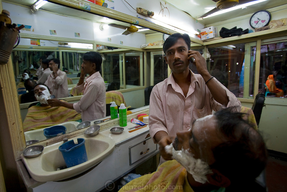 A barber talks on his mobile phone while shaving a client at a barber shop at Santinargar market in Dhakar, Bangladesh.