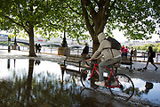 Man cycles through a deep puddle under trees after heavy rain on the riverside walkway. The South Bank is a significant arts and entertainment district, and home to an endless list of activities for Londoners, visitors and tourists alike.