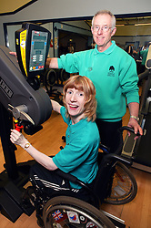 Woman with instructor using upper body ergometer at an inclusive fitness gym,