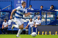 Queens Park Rangers staff and substitutes watch play during the EFL Sky Bet Championship match between Queens Park Rangers and Barnsley at the Kiyan Prince Foundation Stadium, London, England on 20 June 2020.