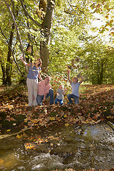 Family playing with autumn leaves by stream in forest, Bavaria, Germany