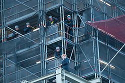 © Licensed to London News Pictures. 18/10/2019. LONDON, UK.  A climate activist (green tights) from Extinction Rebellion observes by a rescue team after scaling the construction scaffolding of the Queen Elizabeth Tower in Westminster.  Parliament Square and the surrounding area has been brought to a standstill as police and emergency services assess the situation.  Photo credit: Stephen Chung/LNP