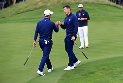 Team Europe's Thorbjorn Olesen and Team Europe's Rory McIlroy bump fists during the Fourballs match on day one of the Ryder Cup at Le Golf National, Saint-Quentin-en-Yvelines, Paris.