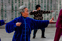 Chinese people practicing tai chi in the early morning in Huangpu Park, Shanghai, China