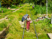 25 NOVEMBER 2017 - YANGON, MYANMAR:  A woman walks on the tracks of the Yangon Circular Train in the countryside outside of Yangon. The Yangon Circular Train is a 45.9-kilometre (28.5 mi) 39-station two track loop system connects satellite towns and suburban areas to downtown. The train was built during the British colonial period, the second track was built in 1954. Trains currently run both directions (clockwise and counter-clockwise) around the city. The trains are the least expensive way to get across Yangon and they are very popular with Yangon's working class. About 100,000 people ride the train every day. A a ticket costs 200 Kyat (about .17¢ US) for the entire 28.5 mile loop.   PHOTO BY JACK KURTZ