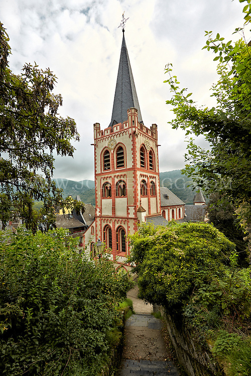 View of St Peter Church from the top of a walkway, and includes mountains and cloudy skies in the background, Bacharach, Germany.