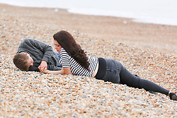 © Licensed to London News Pictures. 08/07/2014. Brighton, UK. A couple relaxing on Brighton beach.Despite temperatures in the next weeks are expected to soar to 86F around the UK with the South Coast predicted to hit record according to the MET the weather is very much cloudy today July 9th. Photo credit : Hugo Michiels/LNP