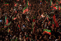 Supporters of Imran Khan, chairman of the Pakistan Tehreek-e-Insaf wave flags and hold up a model of a cricket bat, the party's election campaign symbol, as he speaks from the stage during an election campaign rally in Faisalabad, Pakistan, Sunday, May 5, 2013. Pakistan is scheduled to hold parliamentary elections on May 11, the first transition between democratically elected governments in a country that has experienced three military coups and constant political instability since its creation in 1947.